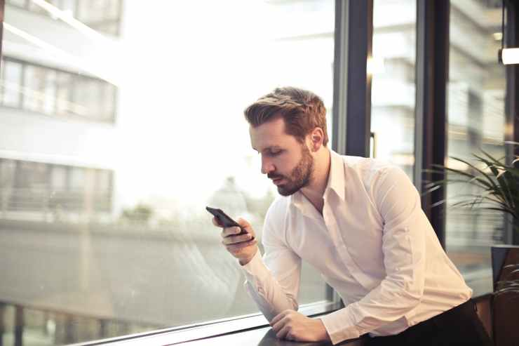 photo of man in white dress shirt holding phone near window